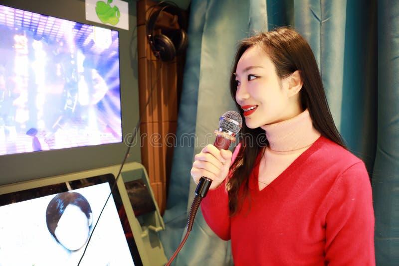 Mulher asiática bonita feliz nova que canta imagem de stock royalty free