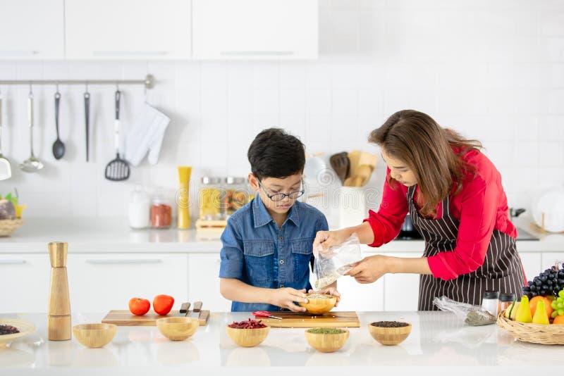 Mulher asiática bonita na camisa vermelha e no avental preto que ensina a fotografia de stock