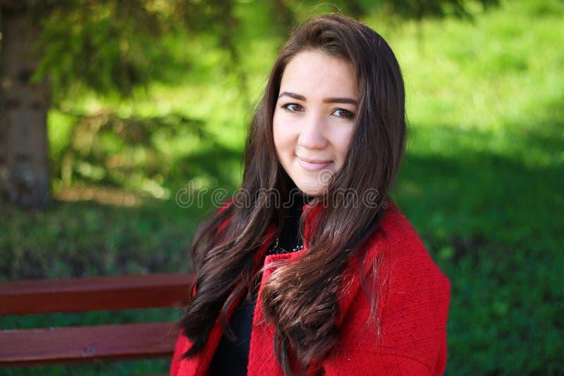 Mulher asiática bonita no revestimento vermelho que senta-se em um banco foto de stock