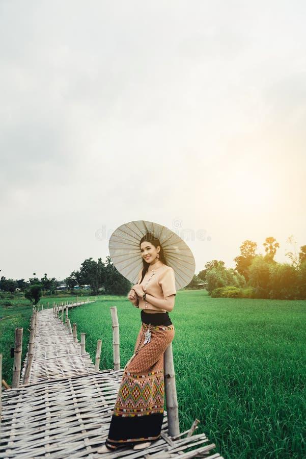 Mulher asiática bonita no vestido local que guarda a posição de papel do guarda-chuva e para apreciar natural na ponte de bamb imagens de stock royalty free