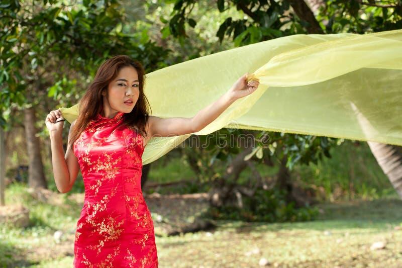 Mulher asiática bonita no vestido tradicional em uma maneira alegre foto de stock royalty free