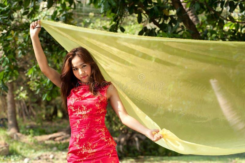 Mulher asiática bonita no vestido tradicional em uma maneira alegre fotos de stock