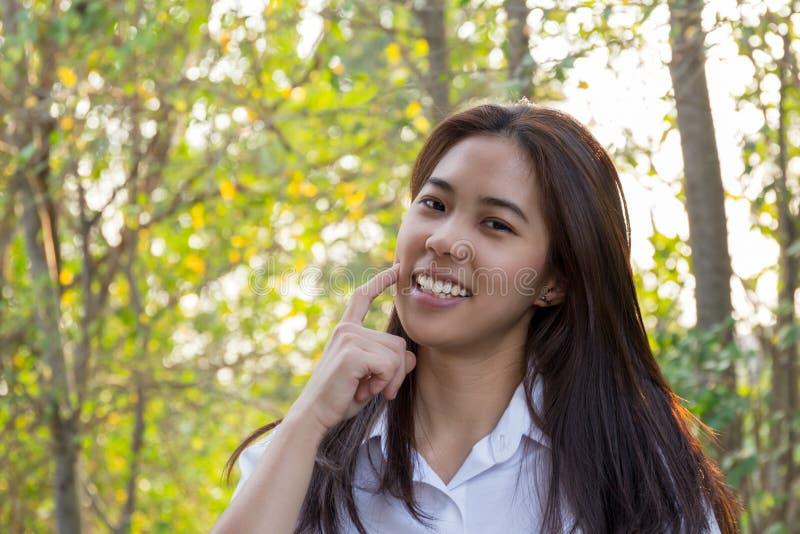 Mulher asiática bonita nova com mão no mordente com árvore e na luz solar no fundo fotos de stock royalty free