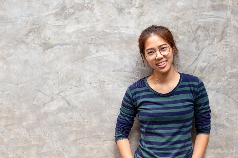 Mulher asiática bonita nova com vidros que sorri no fundo cinzento do muro de cimento, fotos de stock royalty free