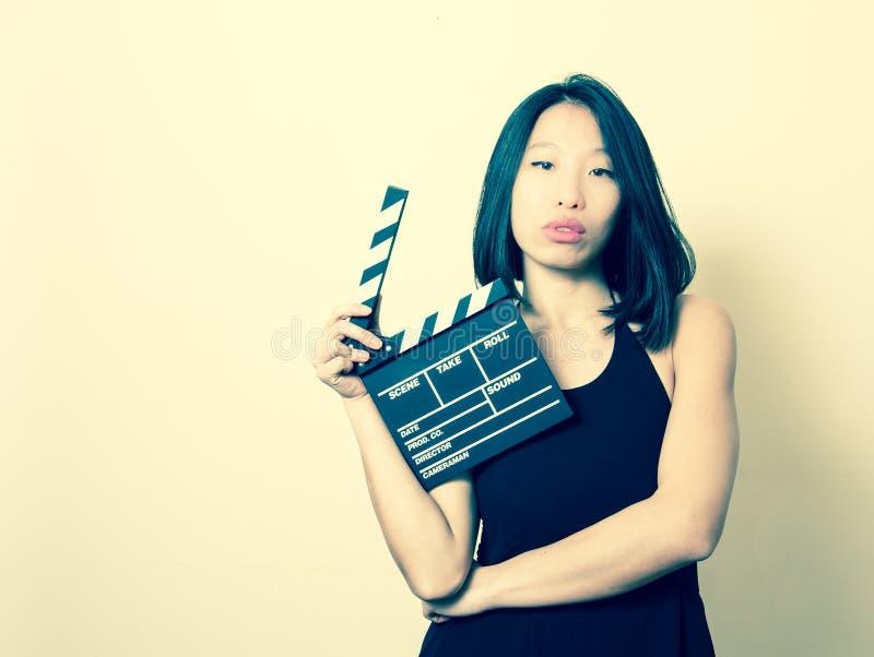 A mulher asiática bonita nova com vintage do clapperboard colore o por fotos de stock royalty free