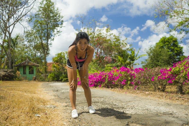 Mulher asiática bonita nova do corredor cansado e sem fôlego esgotada e suado após o exercício de corrida duro no parque da estra foto de stock royalty free