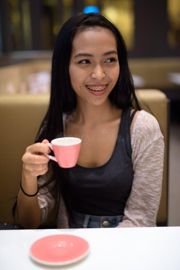 Mulher asiática bonita nova feliz que relaxa dentro da cafetaria imagem de stock