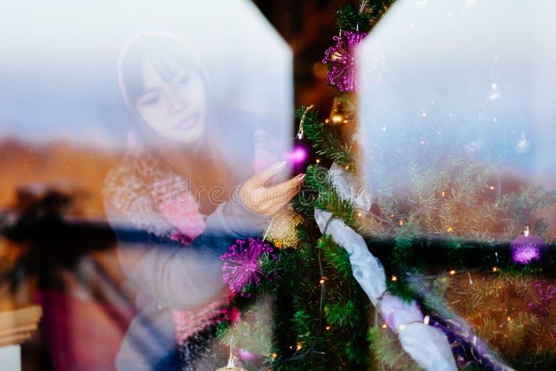 Mulher asiática bonita nova no revestimento do inverno, decorando a árvore de Natal em casa Calha do tiro do retrato da jovem mul fotos de stock