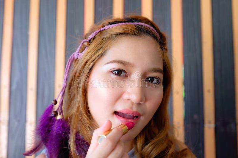 Mulher asiática bonita nova que aplica a composição foto de stock royalty free