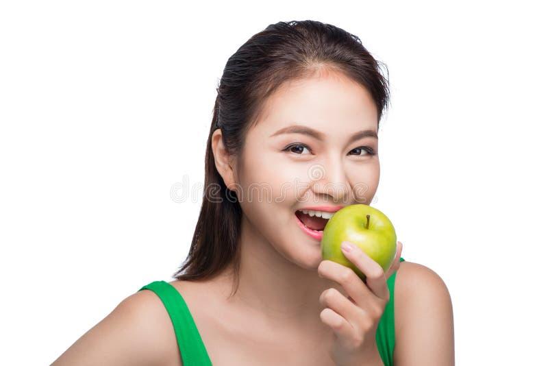 Mulher asiática bonita nova que come a maçã verde fresca nos vagabundos brancos fotografia de stock