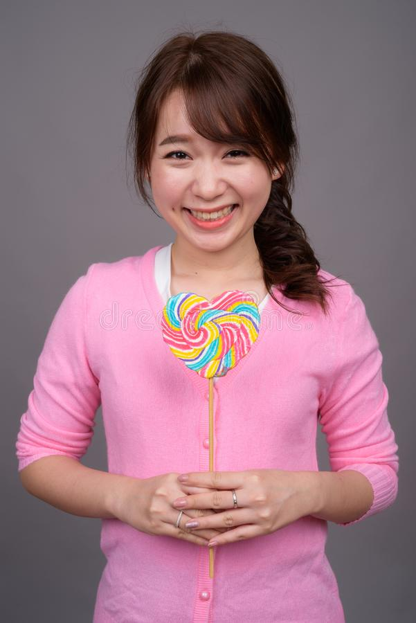 Mulher asiática bonita nova que guarda o pirulito colorido imagem de stock