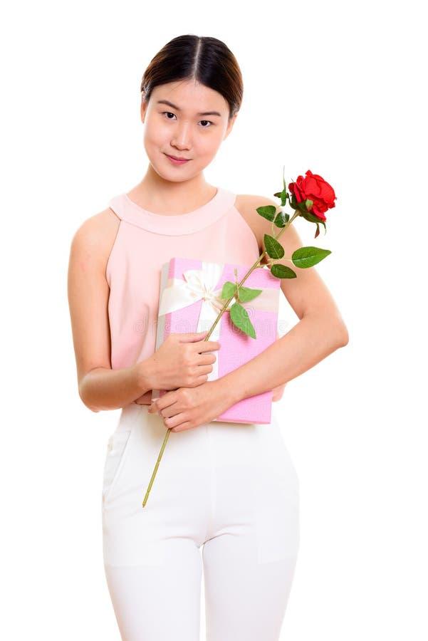 Mulher asiática bonita nova que mantém a rosa vermelha e a caixa de presente prontas fotos de stock