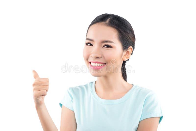 Mulher asiática bonita nova que mostra o polegar isolado no backgro branco imagem de stock