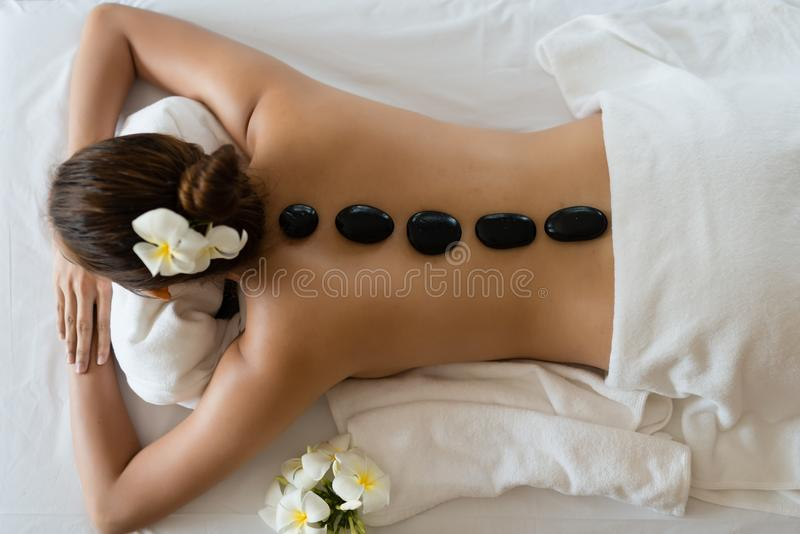 Mulher asiática bonita nova que relaxa na massagem da pedra dos termas S fotografia de stock royalty free