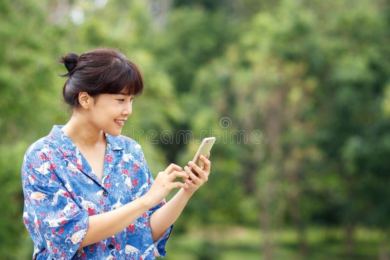 A mulher asiática bonita nova que sorri ao ler, datilografando escreve imagens de stock