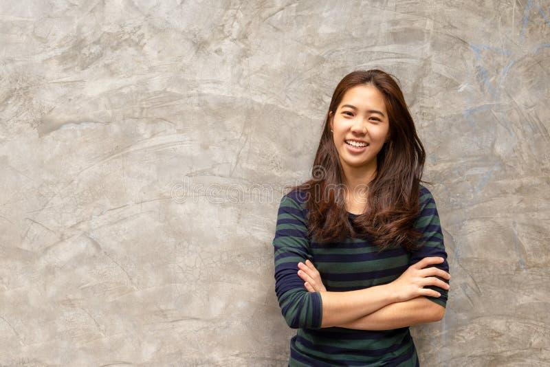 Mulher asiática bonita nova que sorri no fundo cinzento do muro de cimento foto de stock