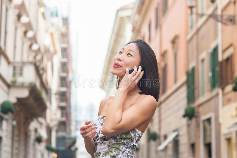 Mulher asiática bonita nova que usa exterior urbano do telefone celular fotografia de stock