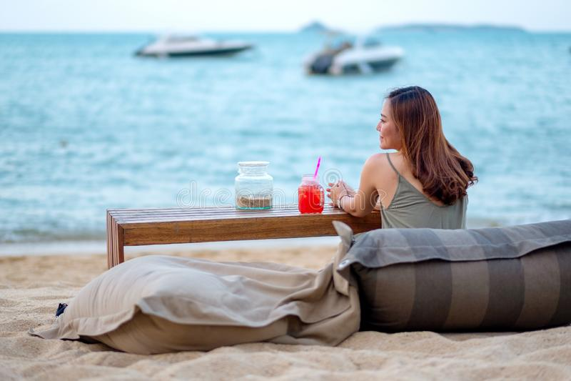 Mulher asiática bonita para apreciar sentar-se na praia pelo litoral imagens de stock