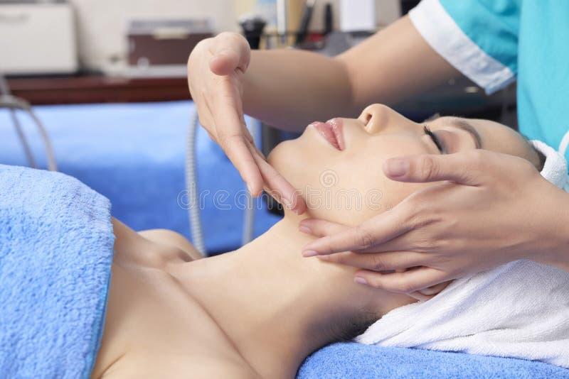 Mulher asiática bonita que aprecia a massagem de cara delicada foto de stock royalty free