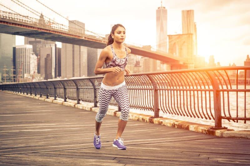 Mulher asiática bonita que corre em New York no tempo do por do sol foto de stock