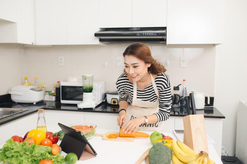 Mulher asiática bonita que cozinha de acordo com a receita no scre da tabuleta fotografia de stock