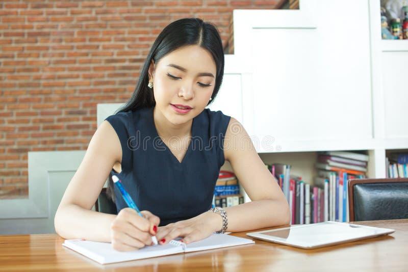 Mulher asiática bonita que escreve um caderno na tabela no inte moderno imagem de stock