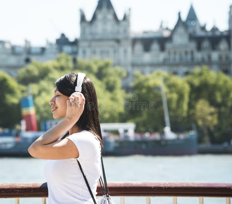 Mulher asiática bonita que escuta a música fotografia de stock