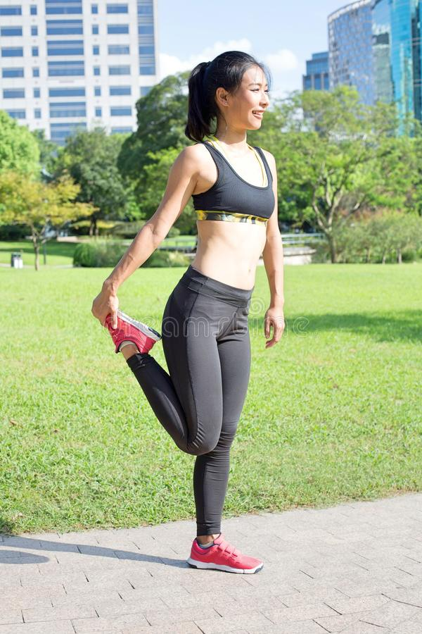 A mulher asiática bonita que estica seus músculos antes dela corre fotografia de stock