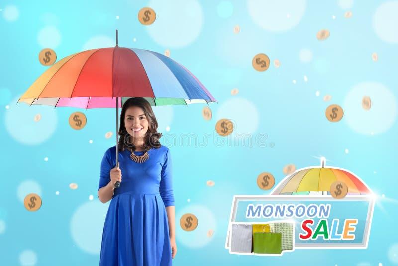 Mulher asiática bonita que guarda o guarda-chuva com a moeda de ouro chuvosa fotos de stock royalty free