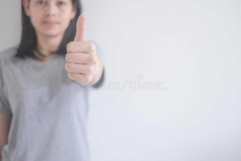 Mulher asiática bonita que mostra os polegares acima em um fundo branco com espaço da cópia foto de stock