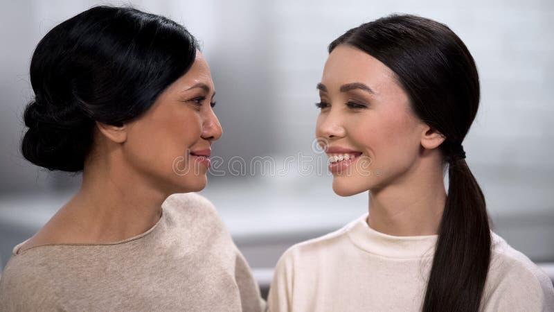 Mulher asiática bonita que olha o tempo da despesa se, da mãe e da filha imagens de stock royalty free