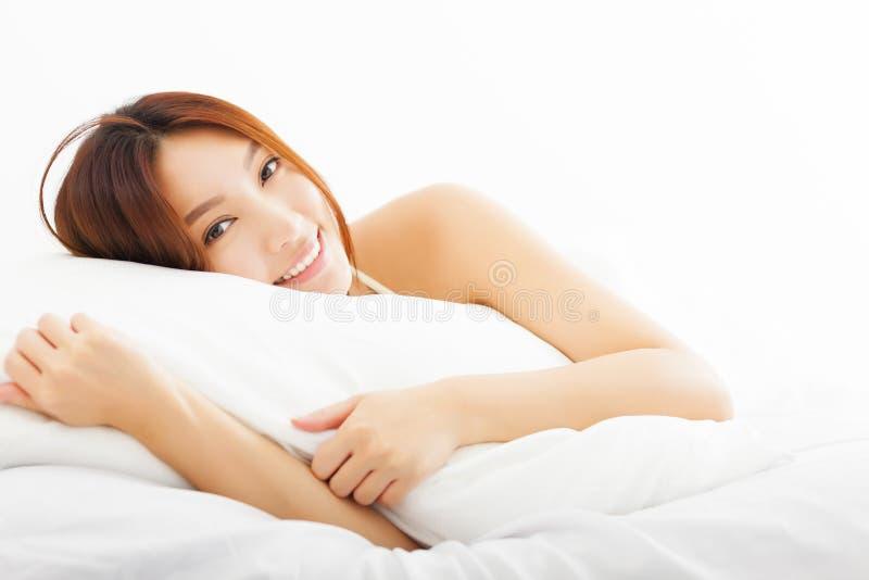 Mulher asiática bonita que relaxa na cama foto de stock