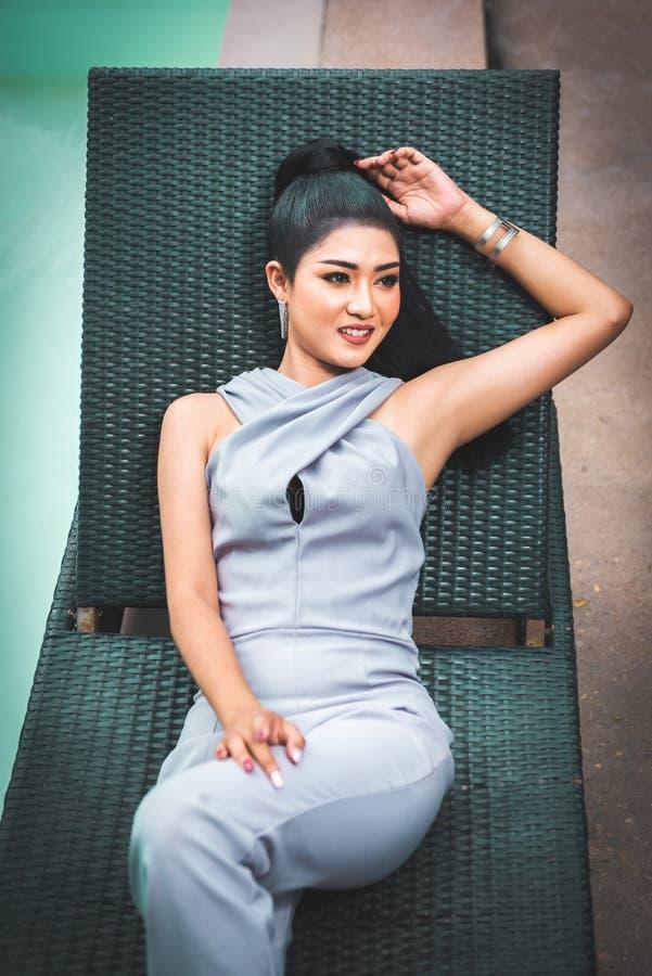 Mulher asiática bonita que relaxa no dobrador chiar e para apreciar o ar fresco ao lado do ool da piscina imagem de stock