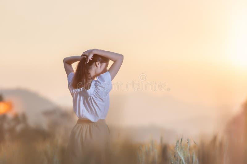 Mulher asiática bonita que tem o divertimento no campo da cevada no verão no tempo do por do sol imagens de stock