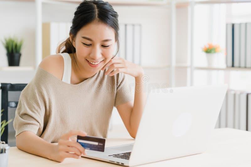Mulher asiática bonita que usa o computador ou o portátil que compram a compra em linha pelo cartão de crédito foto de stock