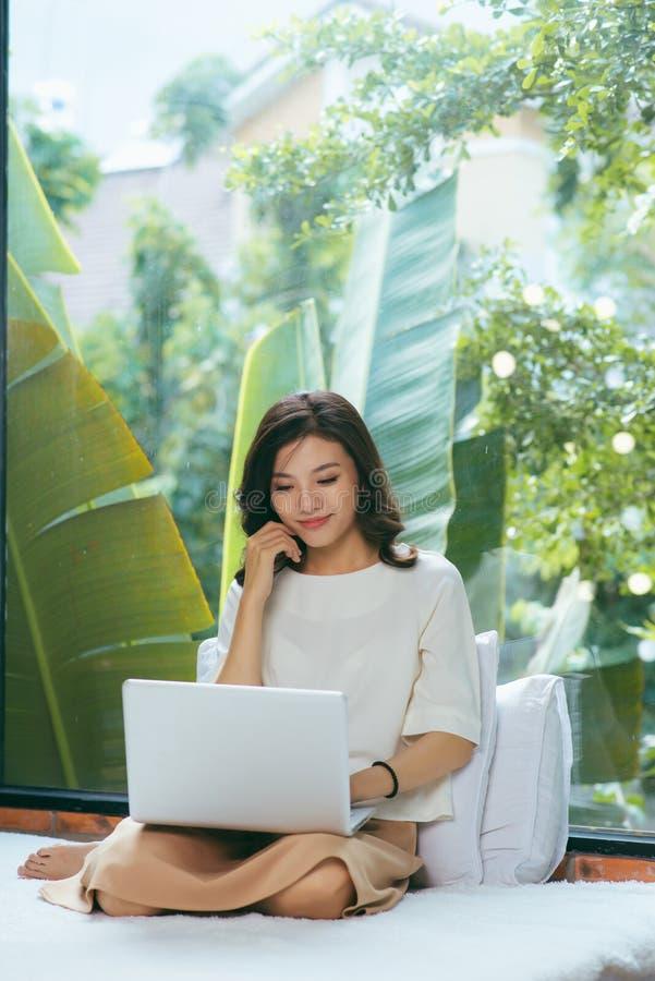 Mulher asiática bonita que usa o laptop na cama na sala e no smil fotografia de stock royalty free
