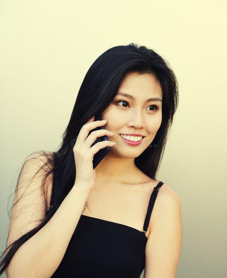 Mulher asiática bonita que verifica suas mensagens fotos de stock royalty free
