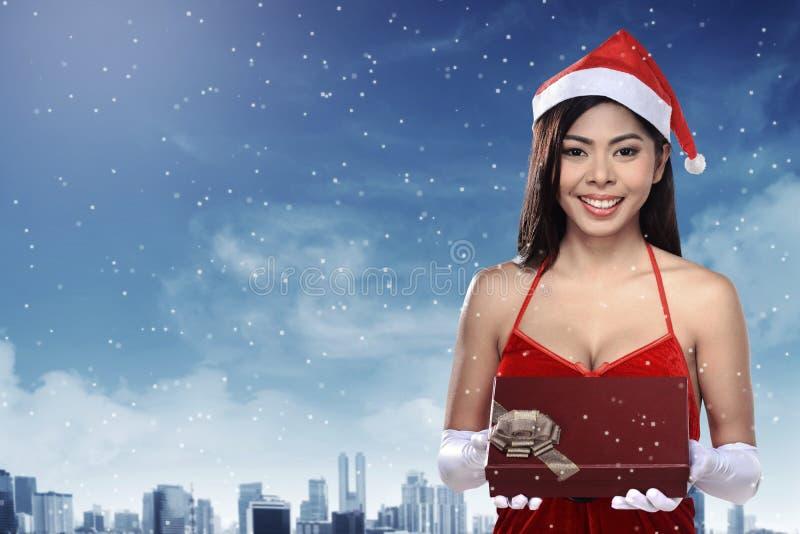 Mulher asiática bonita que veste o traje de Papai Noel que guarda a caixa de presente foto de stock royalty free