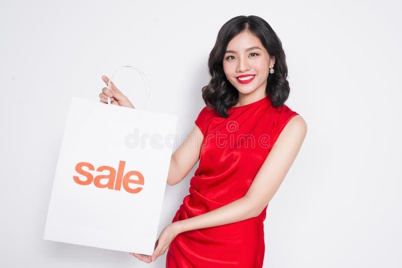 Mulher asiática bonita que veste um vestido vermelho com o saco de compras que está sobre o branco foto de stock