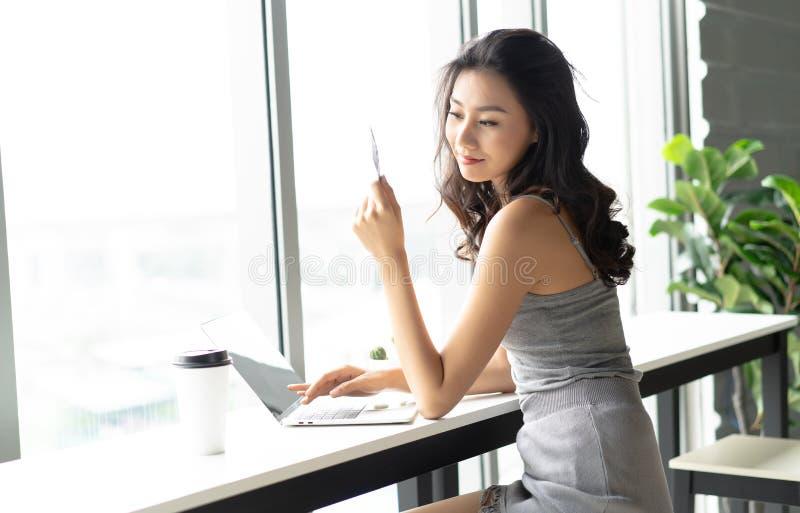 Mulher asiática caucasiano atrativa nova que guarda o cartão de crédito e o u imagem de stock