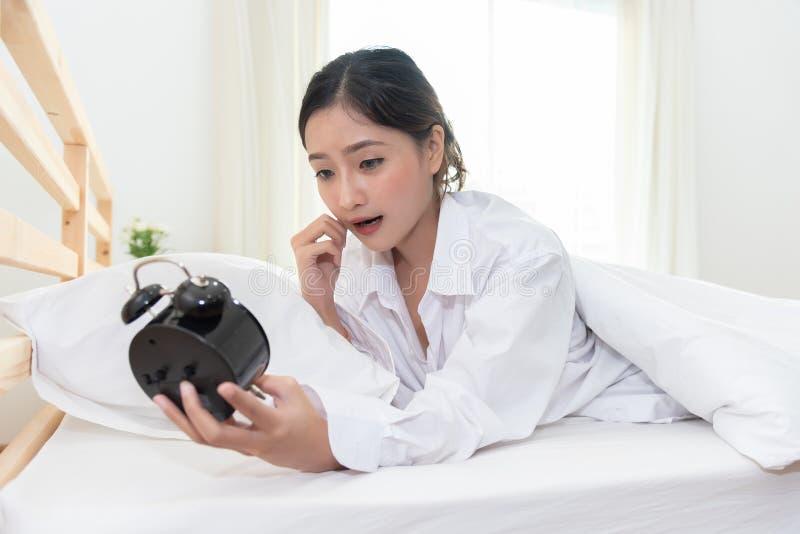 Mulher asiática chocada quando acorde tarde perto para esquecer a ajustar o despertador na noite e a ter a nomeação da reunião e  fotos de stock
