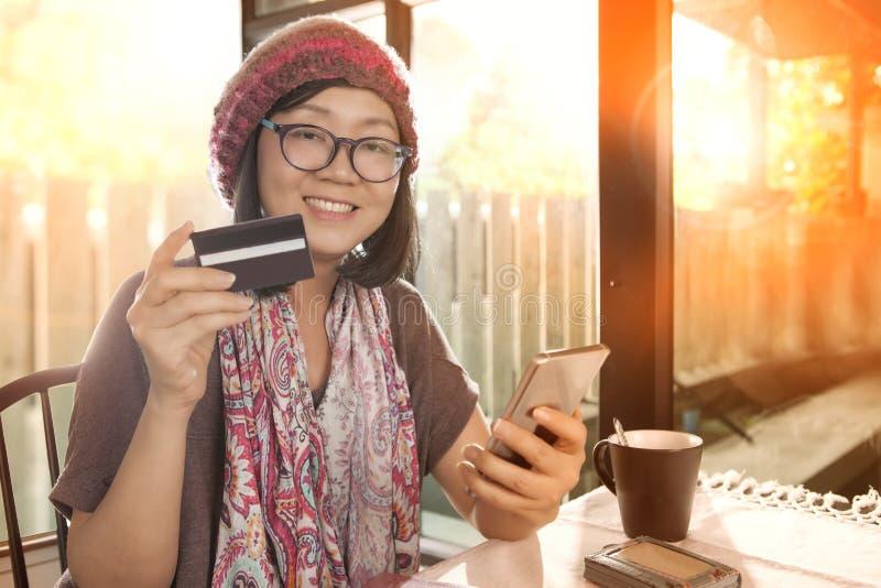 Mulher asiática com cartão de crédito à disposição, compra moderna do estilo de vida na linha imagem de stock royalty free