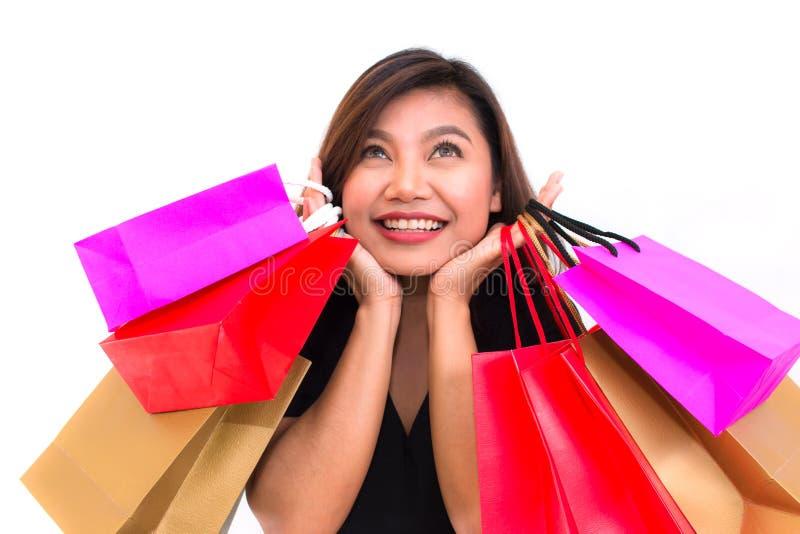 A mulher asiática com colorido leva sacos de compras em suas mãos sorri e felicidade Óculos de sol fotos de stock royalty free