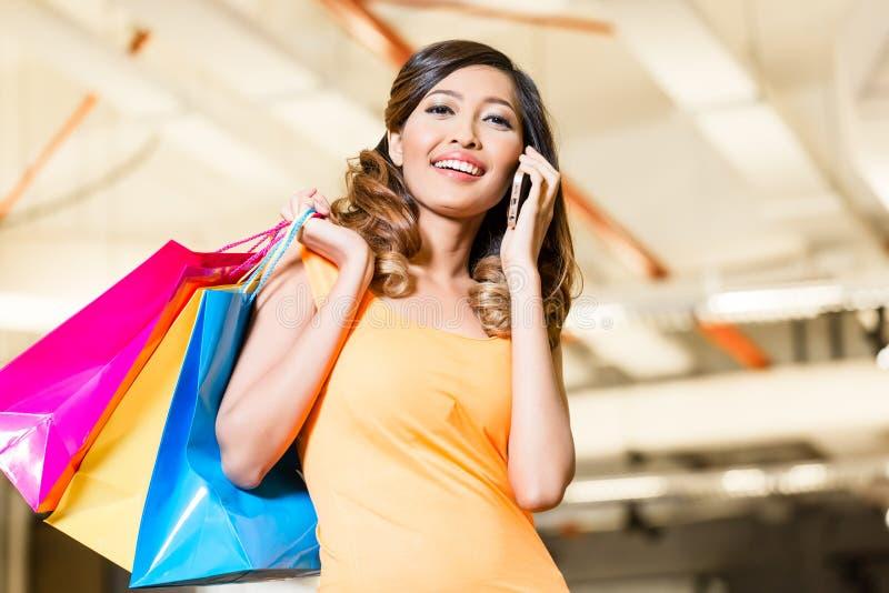 Mulher asiática com forma da compra do telefone foto de stock royalty free
