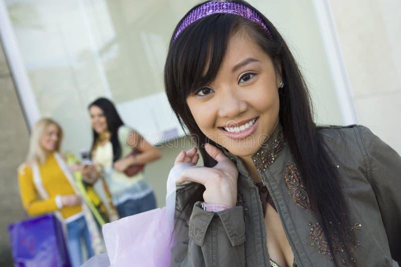 Mulher asiática com saco de compras e amigos no fundo fotografia de stock royalty free