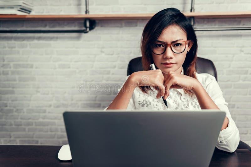 A mulher asiática com vidros e a sua encerram pronto para trabalhar Foco no fac imagens de stock royalty free