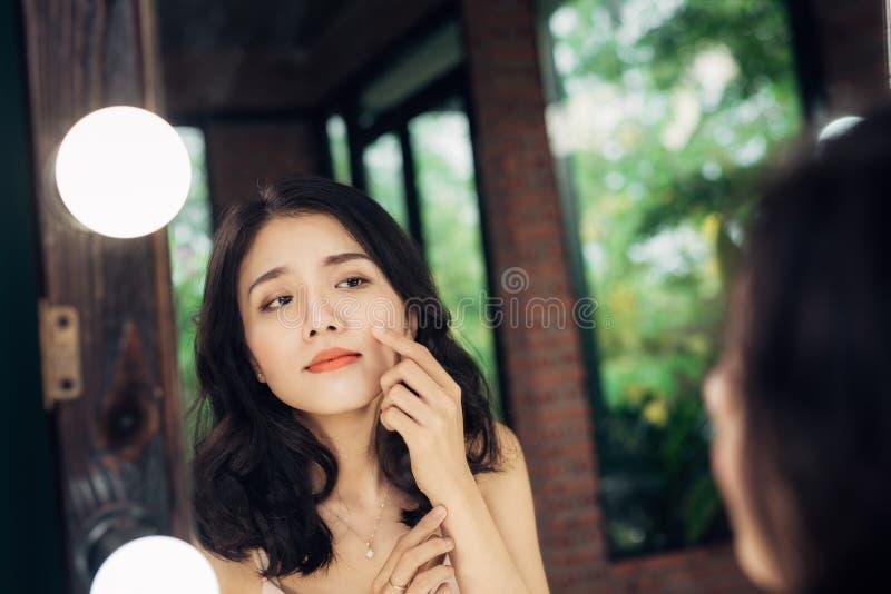 Mulher asiática consideravelmente feliz que olha nsi mesma em um espelho grande em foto de stock