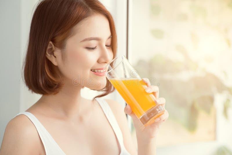 Mulher asiática consideravelmente nova no suco de laranja bebendo da sala brilhante foto de stock royalty free