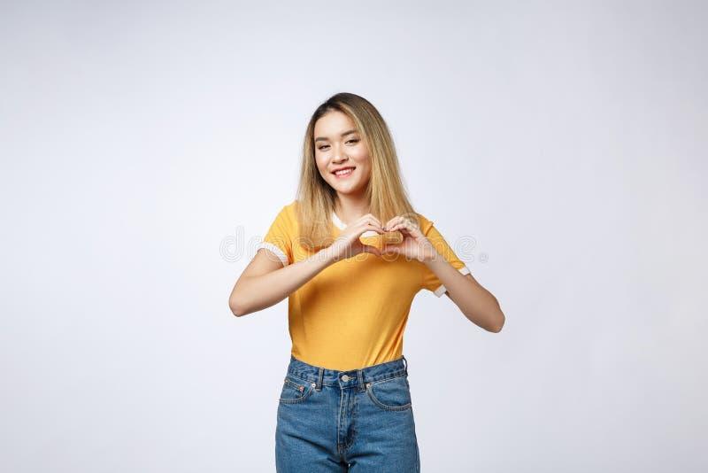 Mulher asiática consideravelmente nova que faz um gesto do coração com seus dedos na frente de sua caixa foto de stock