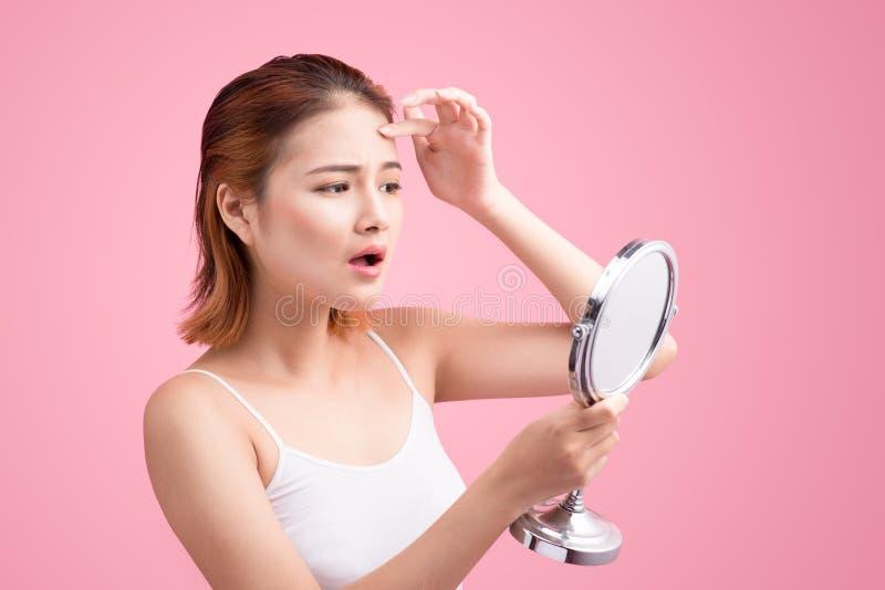 Mulher asiática consideravelmente nova que guarda um espelho, toque e preocupando o ab fotografia de stock royalty free